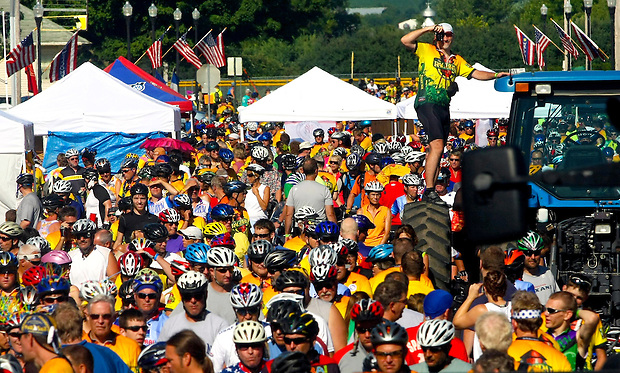 A man climbs a tractor wheel to snap a photograph of the throng of riders descenting upn State Center on RAGBRAI XXXVI.