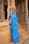Rajasthani girl in blue dress and traditional Rajasthani jewelry at temple entrance in Jaisalmer Fort, Jaisalmer, Rajastan, India --- Model Released