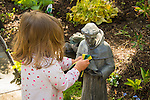 Toddler cleaning St. Francis garden sculpture.