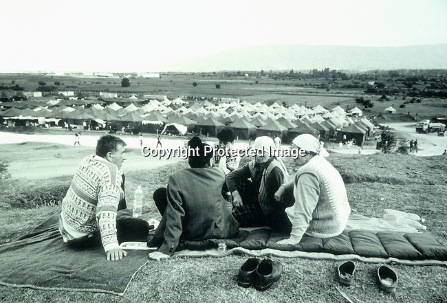 Ethnic Albanian Kosovar refugees on April 21, 1999 in refugee camp in Stankovac, Macedonia. Hundreds of thousands of people fled Serb terror in Kosovo into Albania and Macedonia in early 1999; Red Cross tents; group of refugees sitting talking. .©Per-Anders Pettersson/iAfrika Photos
