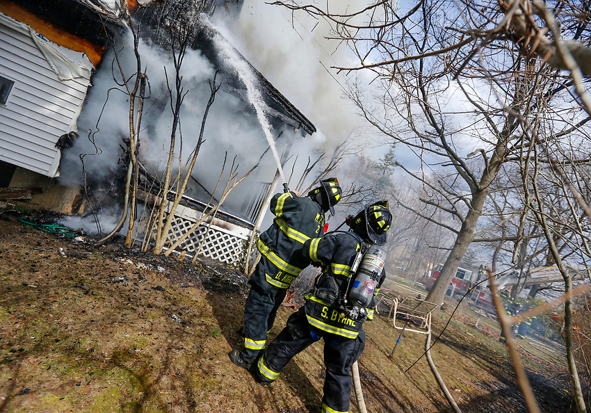 Manasquan FD ex-chief Dave Kircher and firefighter Steve Byrne operate a handline as they a structure fire on Pearce Avenue at about 3 pm on Easter Sunday, April 1, 2018.