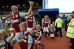 Burnley 1 West Ham United 3, 18/10/2014. Turf Moor, Premier League. Home team players and mascots walking onto the pitch at Turf Moor, home of Burnley FC, on the day the club hosted West Ham United in an English Premier League match. The fixture was won by the visitors by three goals to one watched by 18,936 spectators. The defeat meant that Burnley still had not won a league match since being promoted from the Championship the previous season. Photo by Colin McPherson.