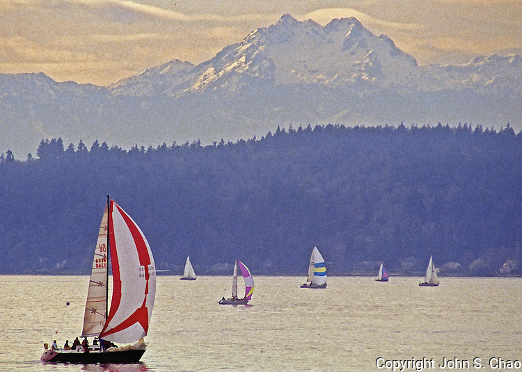Sailboat regatta on Puget Sound, before Brothers Mountain, Olympic Mountain Range, Washington State. Drybrushed watercolor effect applied with Adobe PhotoShop software. Original photograph on Velvia 100 film in 35mm format.