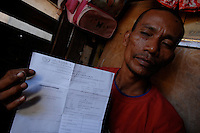 Kidney trader Juanlerio Avila, 38, shows the copy of a tissue typing from from one his clients who is waiting for the call to donate his kidney. Avila, 38 has introduced 70 men to his conatct in recent years and recieved about 10,000 pesos (113 pounds) each time. Men from the Basico port area slum of Manilasell their kidney's for between 70,000 -  90,000 pesos (800 - 1030 pounds).  More than 300 have sold their kidneys in this slum of 16,000 people.<br /> <br /> PHORO BY RICHARD JONES