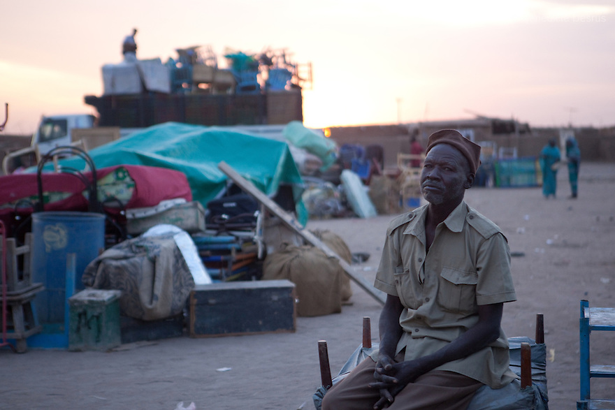 5 january 2011 - Khartoum, Sudan - A Southern Sudanese man in the north sits near his belongings while waiting to load them on a truck as he prepares to leave for the south before the secession referendum, in an area called Soba in Khartoum. The referendum, guaranteed by a 2005 peace deal between north and south which ended Africa's longest civil war, is forecast to result in secession, but exactly how the two countries will begin to disentangle their economies, resources and people is far from clear. Photo credit: Benedicte Desrus