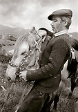 REPUBLIC OF GEORGIA, mid adult man bridling a horse (B&W)