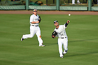 Lakeland Flying Tigers outfielder Jeff McVaney (14) throws the ball in as Chad Wright (4) backs up the play during a game against the Tampa Yankees on April 5, 2014 at Joker Marchant Stadium in Lakeland, Florida.  Lakeland defeated Tampa 3-0.  (Mike Janes/Four Seam Images)