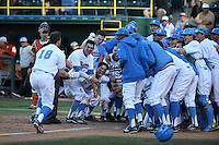 Kort Peterson (18) of the UCLA Bruins is greeted by his teammates after hitting a game wining home run in the bottom of the ninth inning during a game against the Texas Longhorns at Jackie Robinson Stadium on March 12, 2016 in Los Angeles, California. UCLA defeated Texas, 5-4. (Larry Goren/Four Seam Images)