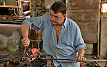A glass workshop at Murano Island outside of Venice, Italy where a man makes a glass rooster