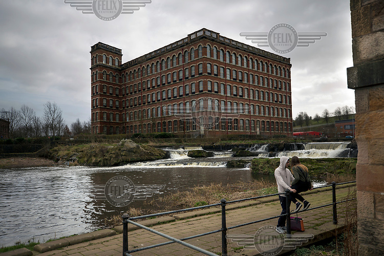 A couple sit near the Abbey Mill, built in 1886 during the town's industrial hey-day making thread for textiles.  Today the site has been restored as a business centre and residential flats.