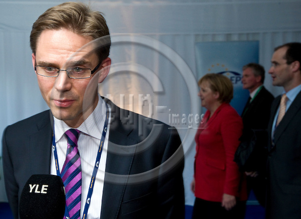 BRUSSELS - BELGIUM - 16 JUNE 2010 -- Jyrki KATAINEN , Deputy Prime Minister and Finance Minister of Finland giving his press conference as the EPP Vice President during the EPP summit. In the background Angela MERKEL, German Federal Chancellor leaving the meeting.  -- PHOTO: Juha ROININEN / EUP-IMAGES