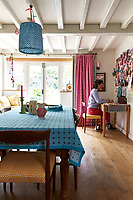 Molly Mahon in the kitchen of her traditional 16th century cottage. The floor has been dug out to provide extra height and the beams are painted white to create a sense of space. The tablecloth, lampshade and curtains are  in Molly Mahon fabrics.