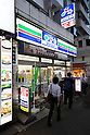 Pedestrians walk past a Three F convenience store in Tokyo on September 2, 2015, Tokyo, Japan. Store operators Lawson Inc. and Three F Co. announced on Monday that they had started to negotiations for a business tie-up that would allow them to work together in product development and procurement. The smaller Three F brand is expected to be maintained and the companies will continue to manage their own distribution. (Photo by Rodrigo Reyes Marin/AFLO)
