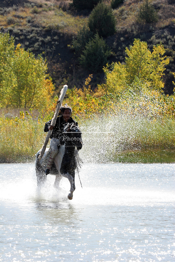 A Native American Sioux Indian on horseback riding across a river on his Indian Pony and staff in South Dakota