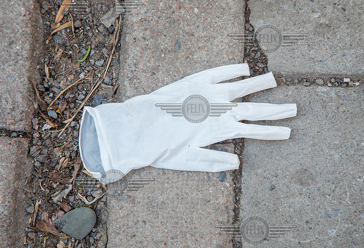 Discarded protective glove on a sidewalk. Norwegian authorites introduced measures to combat the Coronavirus (COVID-19).<br /> <br /> Restriction on public gatherings, closure of schhols, new rules for those serving food and drinks, and fear of further spread of the virus have brought the country to a stand still. <br /> <br /> ©Fredrik Naumann/Felix Features