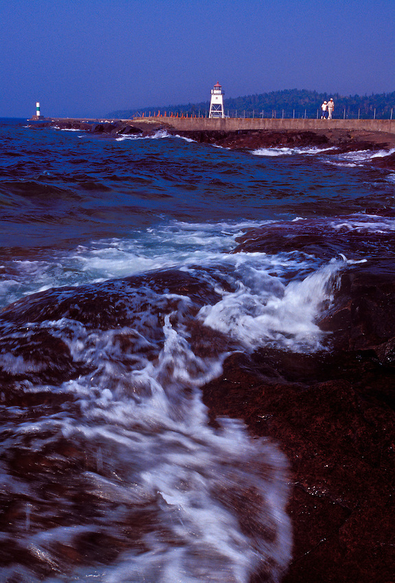 Lake Superior waves crash on the rocky shores of Grand Marais, Minnesota as tourists visit the town's lighthouse.