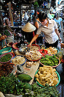 Woman inspecting mushrooms amongst vegetables for sale. Cho Vung Tau (Vung Tau Market), Vung Tau, Vietnam