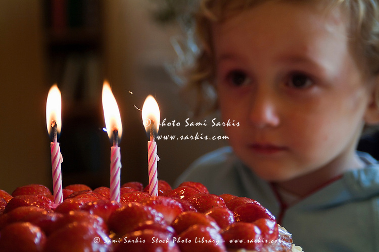 Three year old girl making a wish before blowing out the candles on her birthday cake, France.