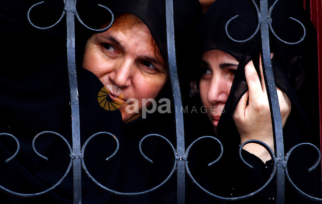 Palestinian women look through a window at the funeral procession of Popular Resistance Committees (PRC) member Khaled Sahmud in the town of Khan Yunis in the southern Gaza Strip on September 7, 2011 a day after he was killed in an Israeli air strike. Photo by Ashraf Amra