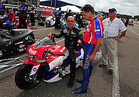 Mar. 9, 2012; Gainesville, FL, USA; NHRA pro stock motorcycle rider Wes Wells (left) talks with Hector Arana during qualifying for the Gatornationals at Auto Plus Raceway at Gainesville. Mandatory Credit: Mark J. Rebilas-