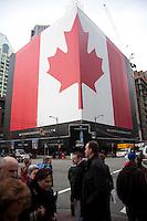 Olympiastadt Vancouver 2010..Kanadische Nationalflagge bedeckt die komplette Fäche eines mehrstöckigen Hochhauses.