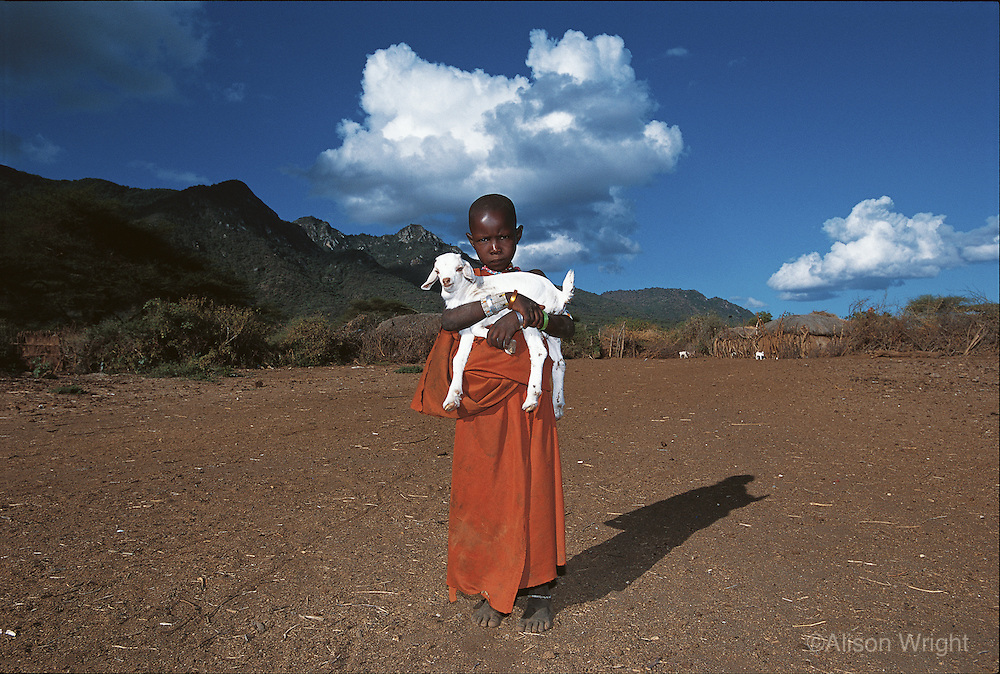 Ndogodo, a four-year-old Maasai girl with her goat. Oltepessi Maasai Village, Tanzania, 2002