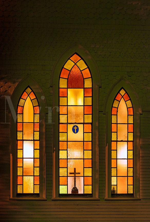 Illuminated church windows at night.