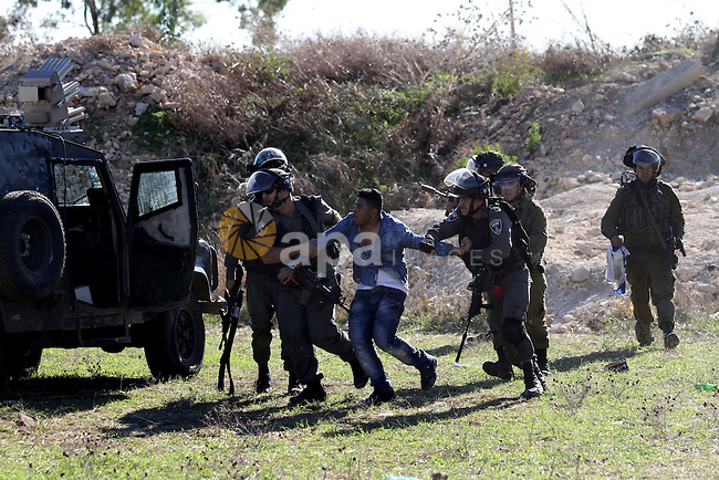 Israeli security forces detain a Palestinian protester during clashes in the West Bank city of Tulkarm November 12, 2015. Israeli undercover forces raided a hospital in the West Bank on Thursday, shooting dead a Palestinian during an attempt to detain another man suspected of carrying out a stabbing, the Palestinian health ministry and doctors said. Photo by Nedal Eshtayah
