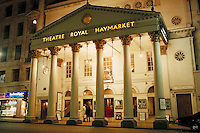 Night view of the illuminated columns and facade of the Haymarket Royal Theater or Theatre Royal Haymarket before one of its famous plays or performances. Acting, drama. London, England.