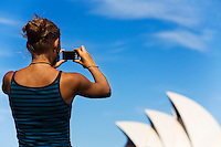 A woman photographs the Opera House on Sydney harbour.  Sydney, New South Wales, AUSTRALIA