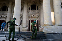 HAVANA, CUBA - April 15: Cuban soldiers wearing face masks disinfect sidewalks and streets in downtown in Havana, Cuba, on April 15, 2020. The military soldiers carry out a disinfection process in the city, applicable in parks, commercial areas, atriums, transportation stations and general public meeting places  decreed by the Government to contain the expansion of COVID. 19. (Photo by Eliana Aponte/VIEWpress)