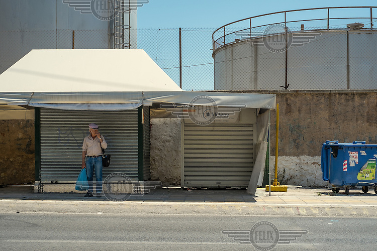 A man waits for a bus at a stop in front of some huge fuel storage tanks, located in an industrial area of Perama, where most of the ship building companies operate.