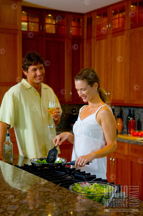 Couple in the kitchen making food  at stove.
