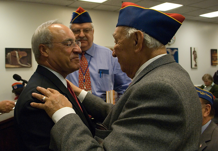 Joe Baca, D-CA., gets a hug from WWII veteran Alfred Galvan during a press conference for the Hispanic Patriots Day on the Hill. WWII book author Virgil Fernandez is in the background.