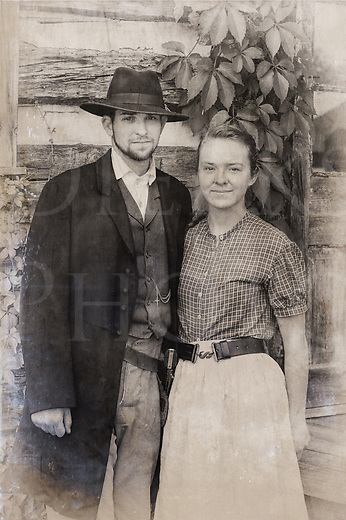 Couple from the 1880's American Wild West, a man and woman in their twenties in reenactor portrayal, modern black and white image processed to create period look.