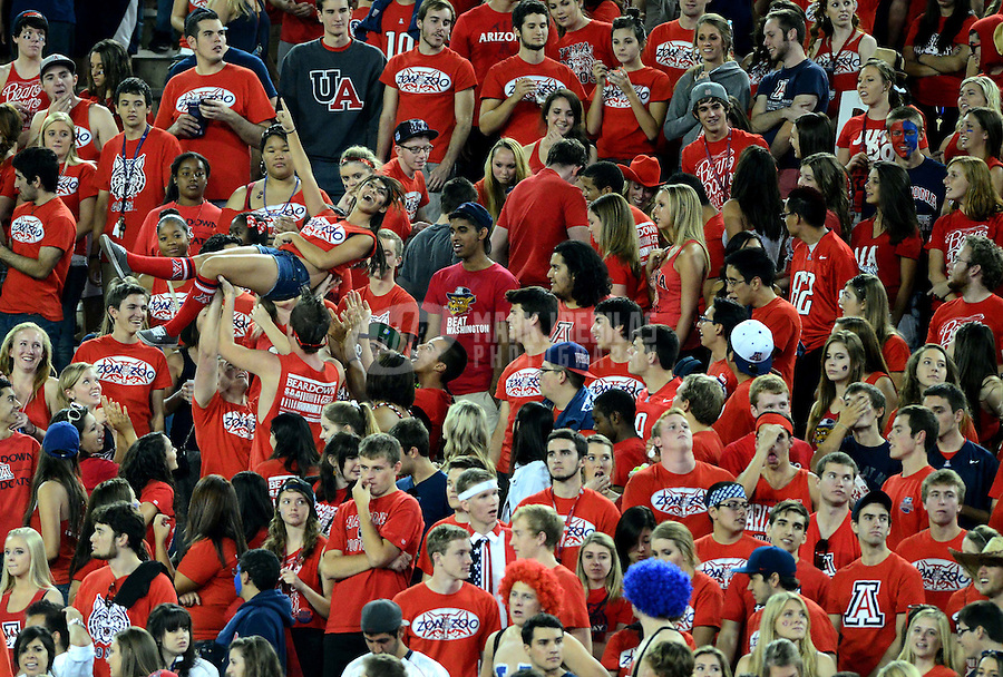 Oct. 20, 2012; Tempe, AZ, USA; Arizona Wildcats fans in the grandstands celebrate a touchdown in the student section in the second half against the Washington Huskies at Arizona Stadium. Arizona defeated Washington 52-17. Mandatory Credit: Mark J. Rebilas-