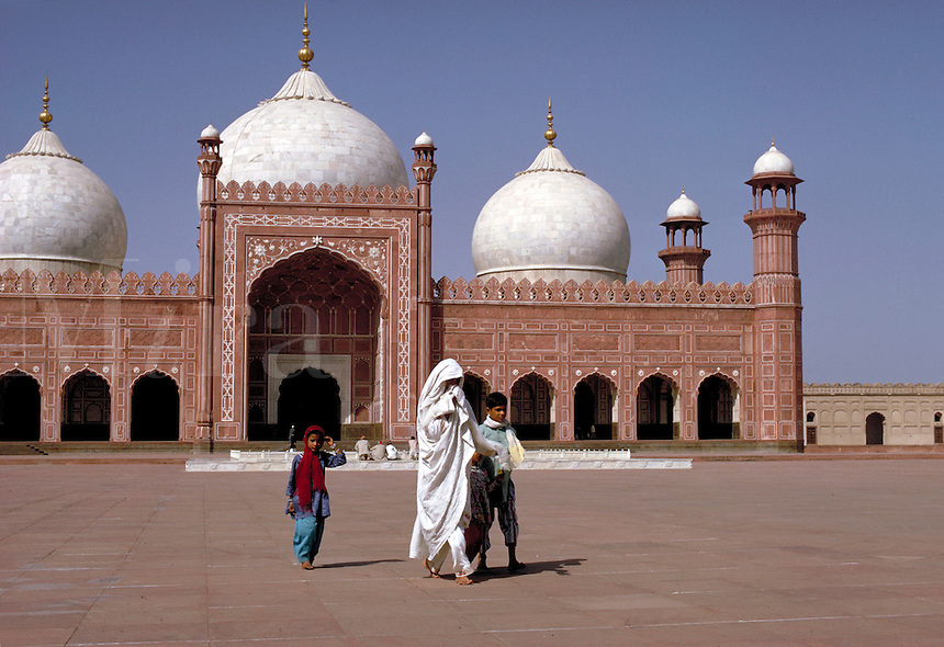 Frontal view of the Shah Mosque, also known as the Royal Mosque, with a few visitors and worshipers walking through its front courtyard clad in white, flowing robes. Lahore, Pakistan Shah Mosque.