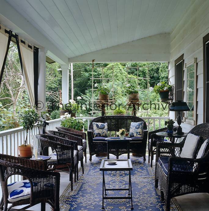 The veranda is filled with black wicker furniture upholstered in a variety of blue and white fabric and is a perfect spot for entertaining