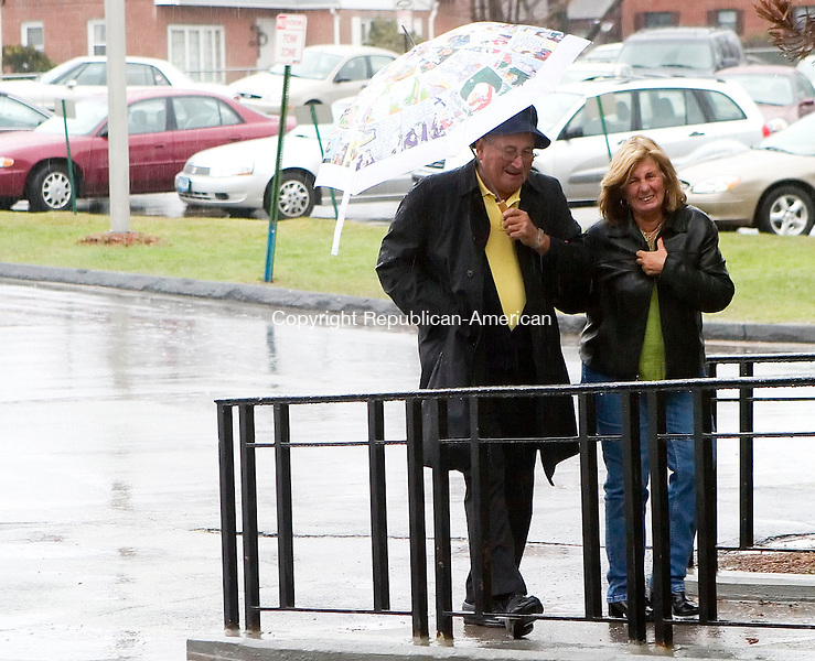 WATERBURY, CT- 15 APRIL 07- 041507JT07- <br /> Richard Jackman and Mary McWeeney share an umbrella as they walk in the rain in front of Kennedy High School in Waterbury on Sunday as a Nor'easter blew through the area with strong winds and excessive rain. <br /> Josalee Thrift Republican-American