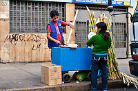 A street vendor prepares stalks of sugar cane for sale as a snack.