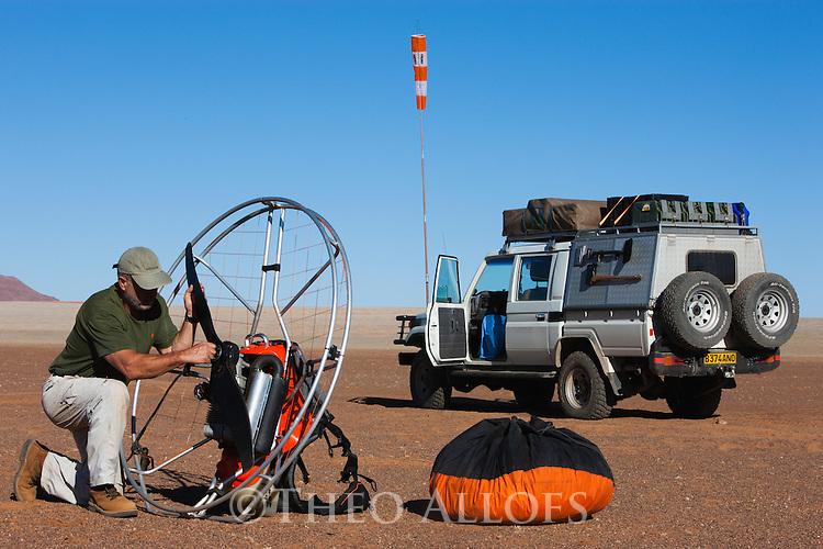 Namibia, Namib Desert, Namibrand Nature Reserve, Theo Allofs taking his paraglider engine apart after flight over the desert
