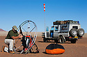 Namibia, Namib Desert, Namibrand Nature Reserve, Theo Allofs taking his paraglider engine apart after flight over the desert