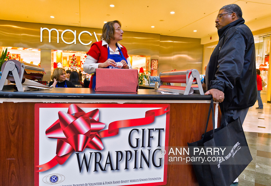 Dec. 12, 2012 - Garden City, New York, U.S. - EILEEN GONZALEZ, of Northport, wraps a gift brought by FLOYD HERRING, of Valley Stream, while she helps the Merrick Kiwanis Club, a community service group, gift wrap presents at Roosevelt Field mall in Long Island to raise funds to use for charity, during the busy winter holiday shopping season. She was one of several members of Meadowbrook Women's Initiative who helped out at the booth. Some ways Kiwanis helps the community are by providing food, clothing, and school supplies to those in need, sending children to Kamp Kiwanis, providing scholarships and hosting a Harvest Ball for senior citizens.