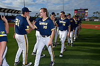 Michigan Wolverines pitchers Michael Hendrickson (30) and Oliver Jaskie (36) high fives teammates, including Evan Hill (21) after the second game of a doubleheader against the Canisius College Golden Griffins on February 20, 2016 at Tradition Field in St. Lucie, Florida.  Michigan defeated Canisius 3-0.  (Mike Janes/Four Seam Images)