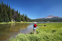 Girl fishing from shore along channel at Sparks Lake, Broken Top Mountain in background, Cascade Lakes, Oregon, USA