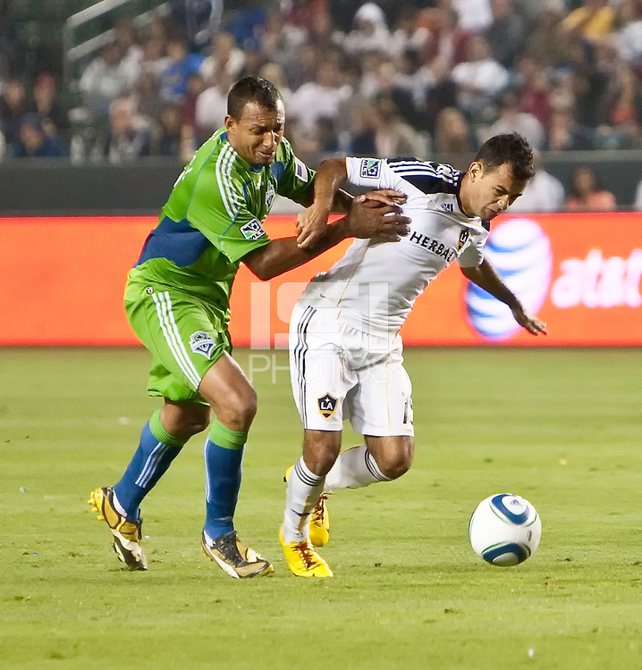Seattle Sounders defender Tyrone Marshall (14) battles LA Galaxy midfielder Juninho (19) for the ball during the second half of the game between LA Galaxy and the Seattle Sounders at the Home Depot Center in Carson, CA, on July 4, 2010. LA Galaxy 3, Seattle Sounders 1.