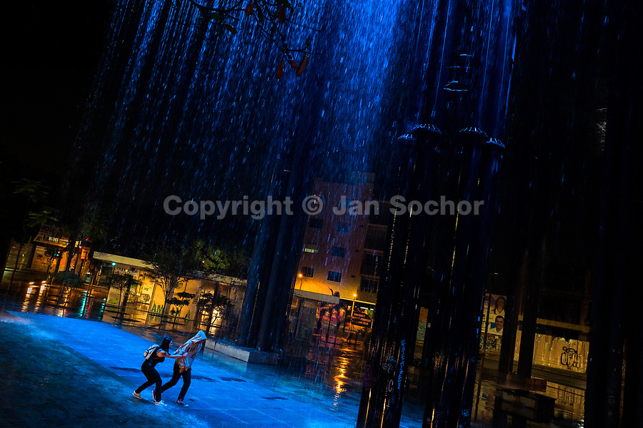 A young Colombian couple, chasing each other, play around in the rain curtain waterfall in the Las Chimeneas park in Itagüí, Colombia, 13 October 2019.