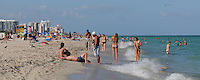 People enyoying the sun sand and warm ocean waters of beautiful South Beach, Miami Beach,  Florida.