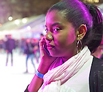 At Bryant Park's ice skating rink that night, a skater talks on her cell phone at the busy, colorful rink. Manhattan, New York, USA. November 9, 2013.