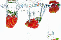 Strawberries fruit splashing underwater, white background, studio